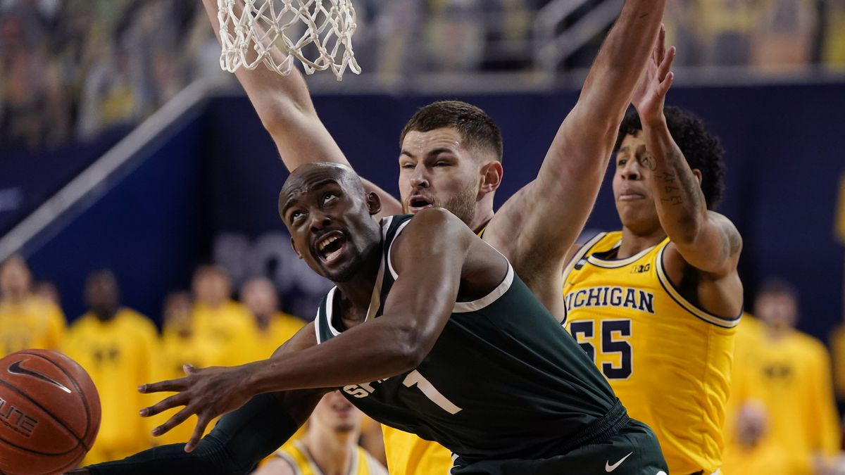 Michigan State guard Joshua Langford (1) is defended by Michigan center Hunter Dickinson,...