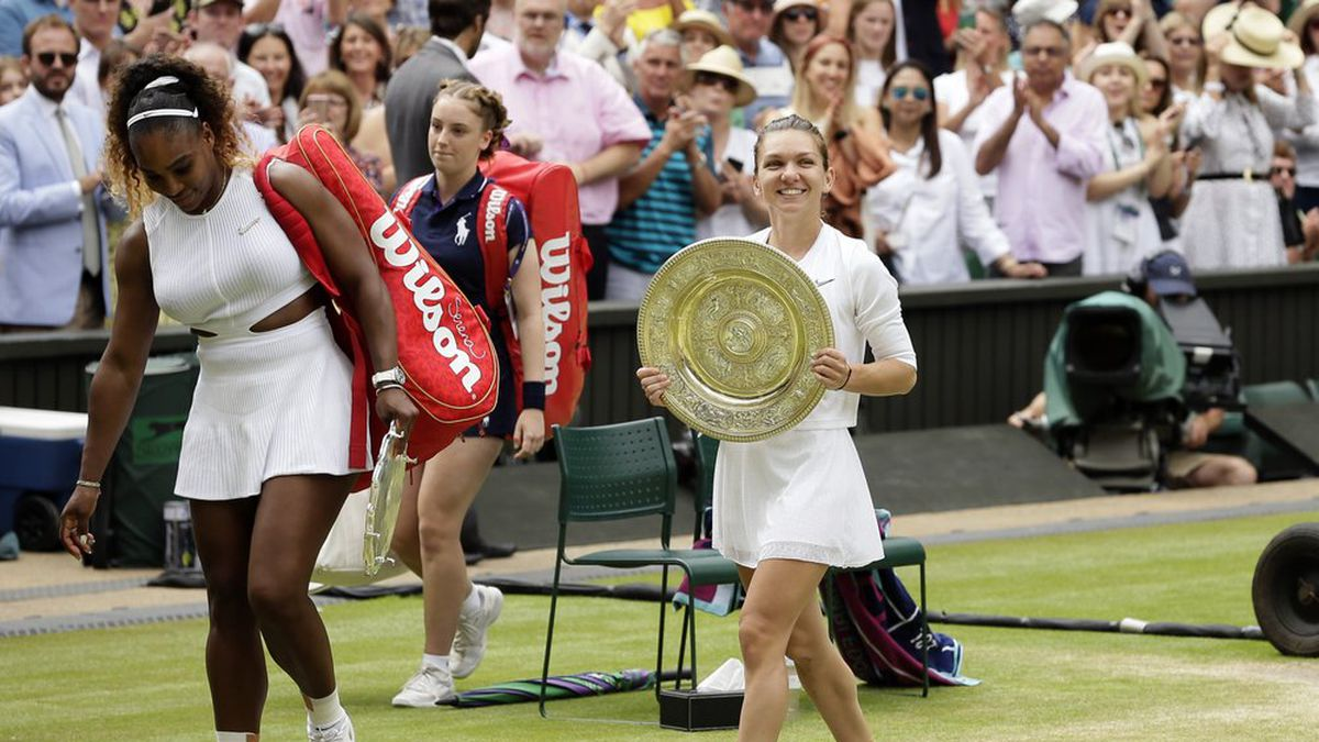 Romania's Simona Halep walks away with her trophy after defeating United States' Serena Williams, left, in the women's singles final match on day twelve of the Wimbledon Tennis Championships in London, Saturday, July 13, 2019. (AP Photo/Tim Ireland)