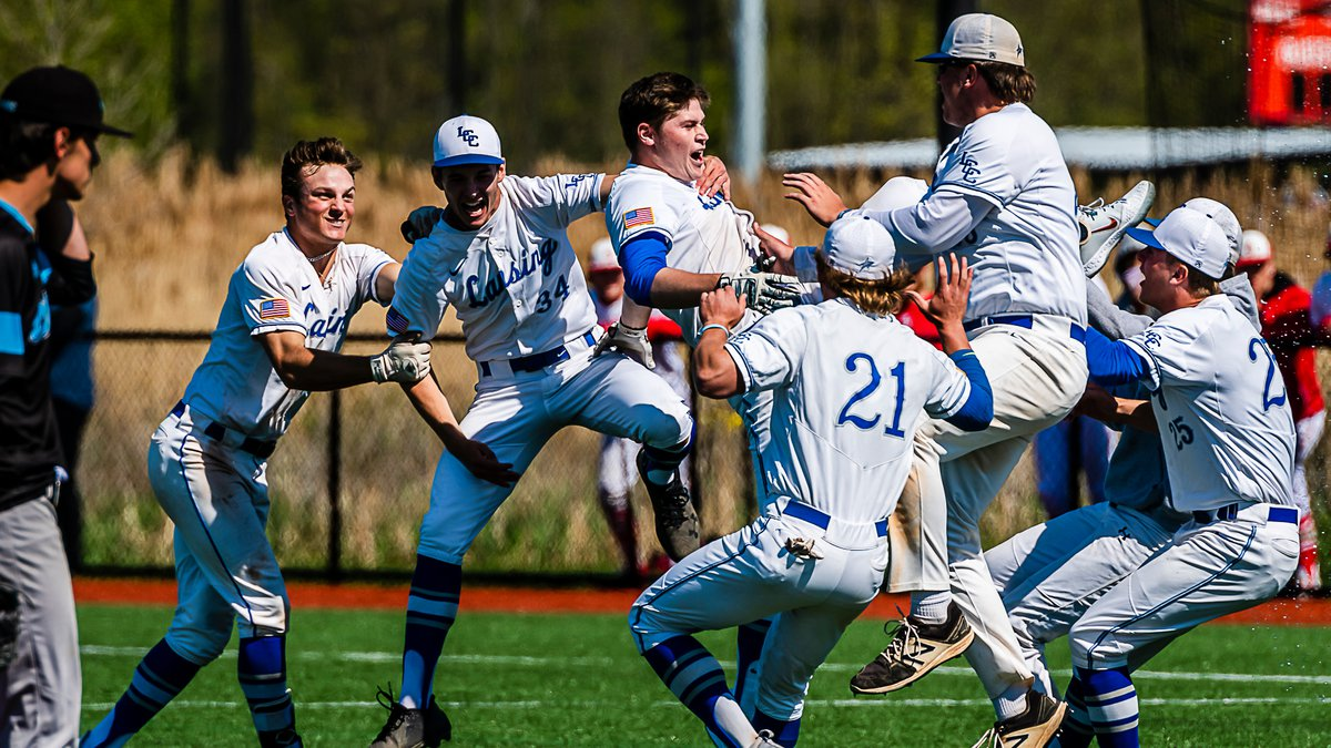 Michael Stygles, top center, of LCC is knocked off his feet by celebrating teammates after he...