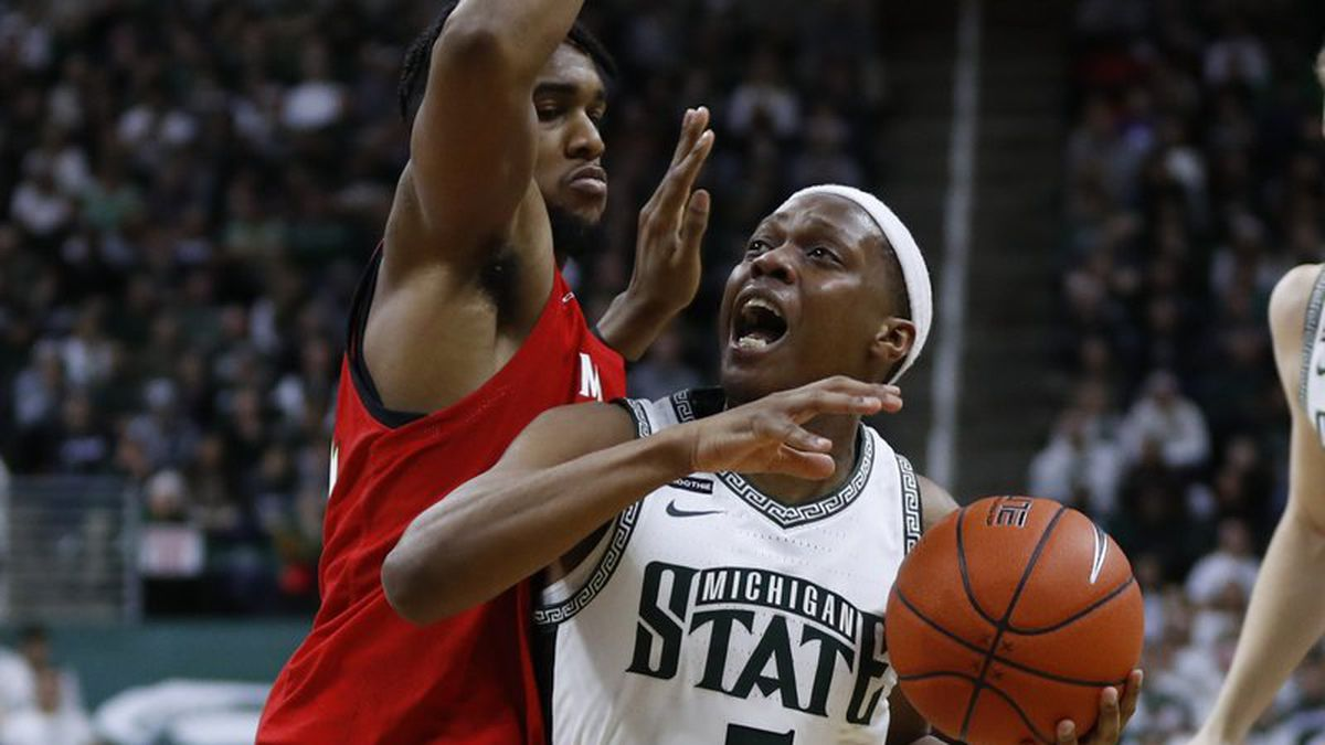 Michigan State guard Cassius Winston (5) drives on Maryland forward Donta Scott (24) in the...