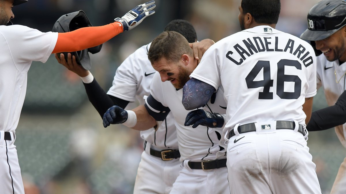 Detroit Tigers' Robbie Grossman, middle, is congratualted by teammates after walking in the...