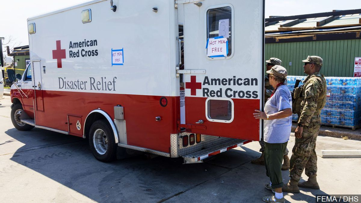 American Red Cross Disaster Relief personnel provide hot meals to disaster survivors and...