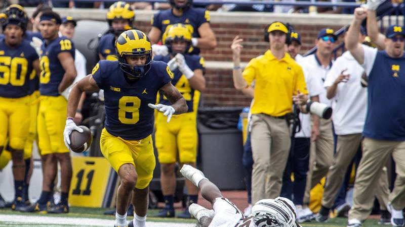 Michigan wide receiver Ronnie Bell (8) beats Western Michigan safety Delano Ware (26) to a...