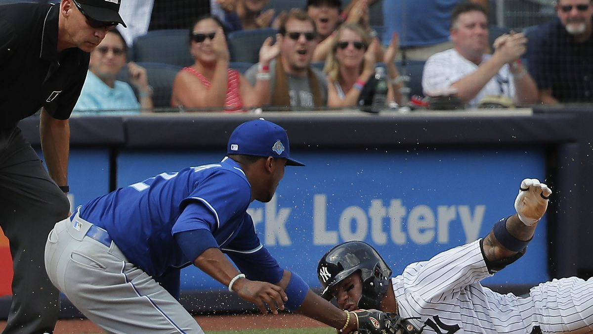 New York Yankees' Gleyber Torres, right, is tagged out by Kansas City Royals third baseman Alcides Escobar (2) as he attempts to stretch a double into a triple during the seventh inning of a baseball game, Saturday, July 28, 2018, in New York. Didi Gregorius scored on the play. (AP Photo/Julie Jacobson)