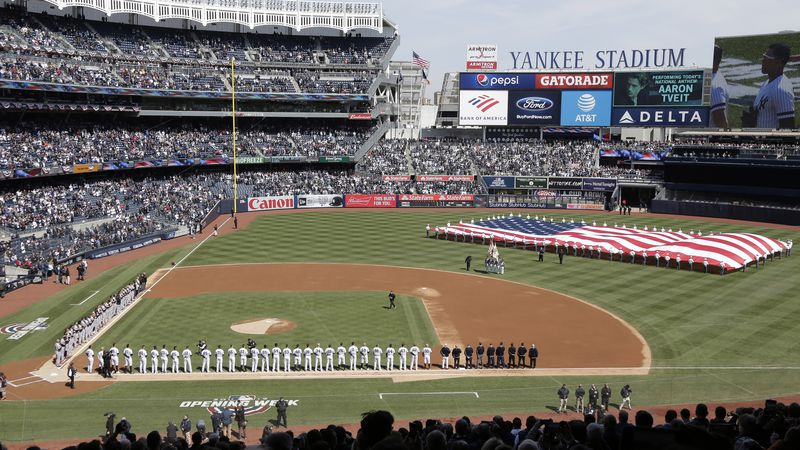 FILE - In this March 28, 2019, file photo, a large flag is unfurled during the national anthem...