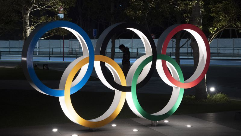 A man is seen through the Olympic rings in front of the New National Stadium in Tokyo, Tuesday,...