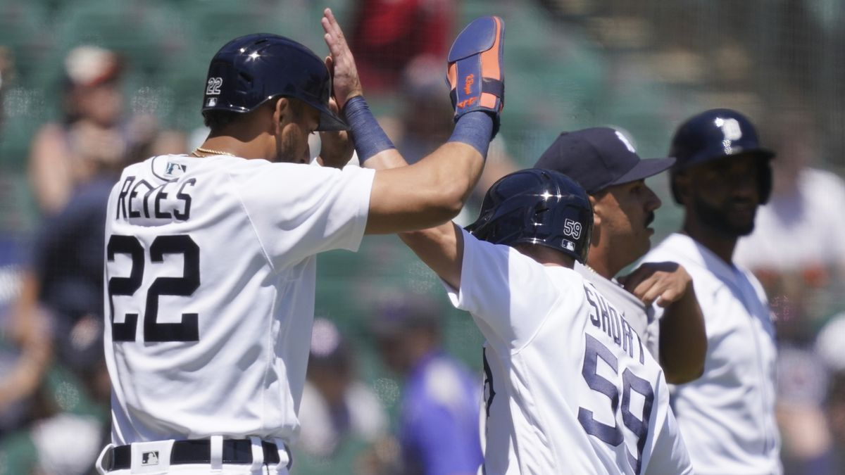 Detroit Tigers' Victor Reyes (22) high fives teammate Zack Short after they both scored on...