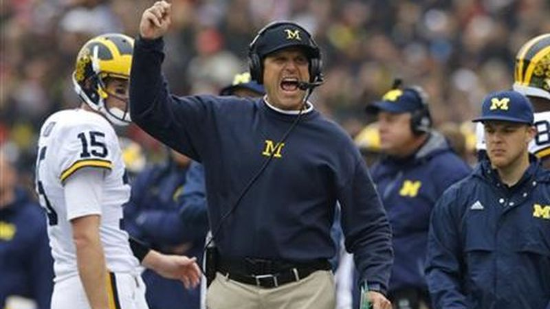 FILE - In this oct. 3, 2015, file photo, Michigan head coach Jim Harbaugh calls for a flag in...