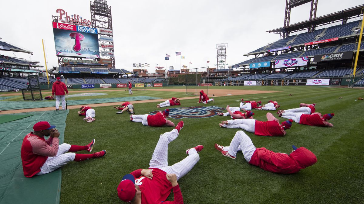 FILE - In this April 7, 2017, file photo, members of the Philadelphia Phillies stretch before the team's baseball game against the Washington Nationals in Philadelphia. Five players for the Philadelphia Phillies have tested positive for COVID-19 at the team's spring camp in Florida, prompting the club to indefinitely close the complex. The team also said Friday, June 19, 2020, that three staff members at the camp have tested positive. The club didn't identify any of those affected.(Matt Rourke | AP Photo/Matt Rourke, File)