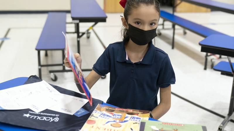 IMAGE DISTRIBUTED FOR MACY'S INC. - Students at Bernard Black Elementary School receive books...