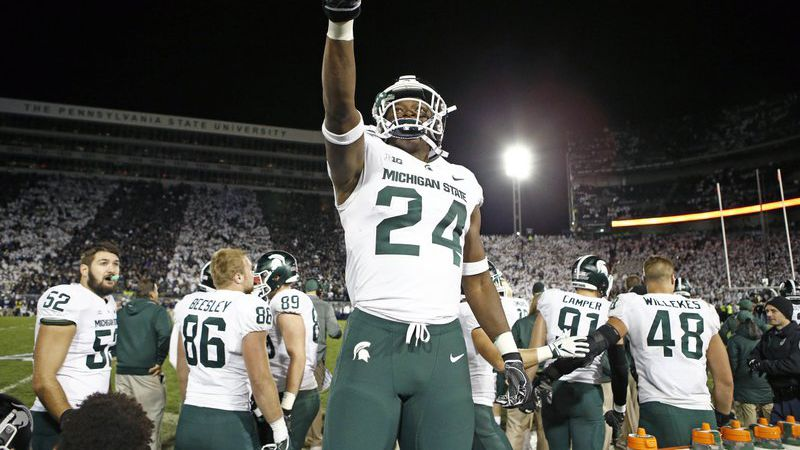 Michigan State's Elijah Collins (24) stands on the bench and celebrates after his team scored...