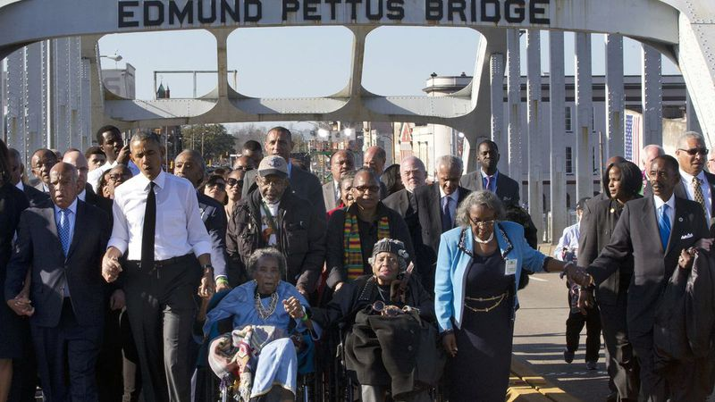 """In this March 7, 2015, file photo, singing """"We Shall Overcome,"""" President Barack Obama, third..."""
