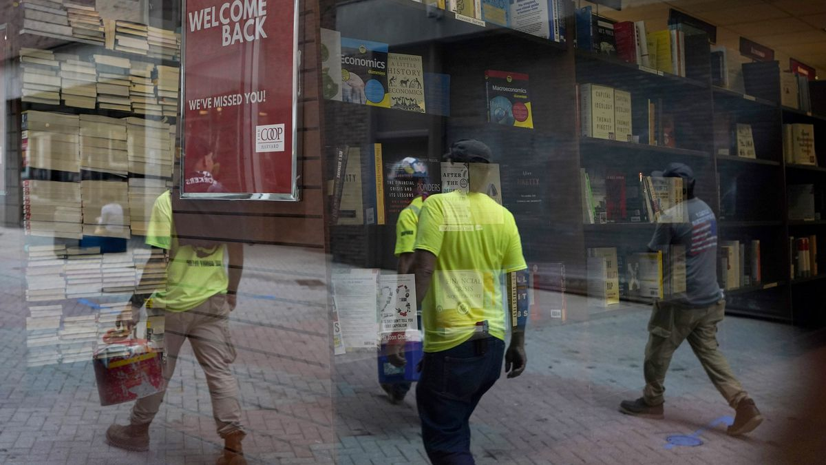 Workers are reflected in a window of a bookstore, Monday, Sept. 28, 2020, in the Harvard Square...