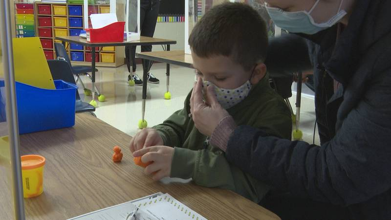 Staci Brown fixes her son Landon's mask during his school's open house.