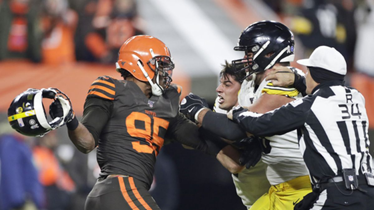 Cleveland Browns defensive end Myles Garrett, left, gets ready to hit Pittsburgh Steelers quarterback Mason Rudolph, second from left, with a helmet during the second half of an NFL football game on Thursday, Nov. 14, 2019, in Cleveland. The Browns won 21-7. (AP Photo/Ron Schwane)