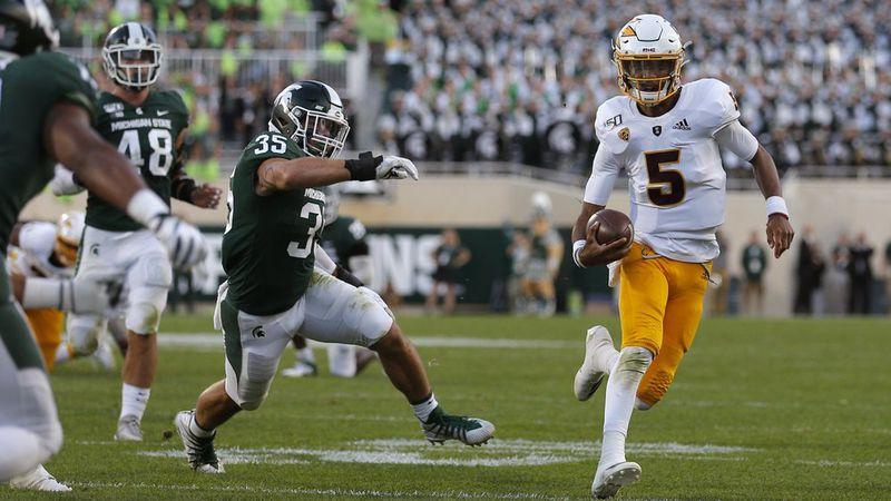 Arizona State quarterback Jayden Daniels, right, scrambles for a first down against Michigan...