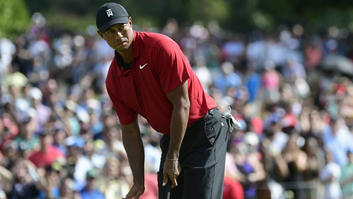 Tiger Woods motions for his putt for birdie to slow down as it passes the ninth hole during...