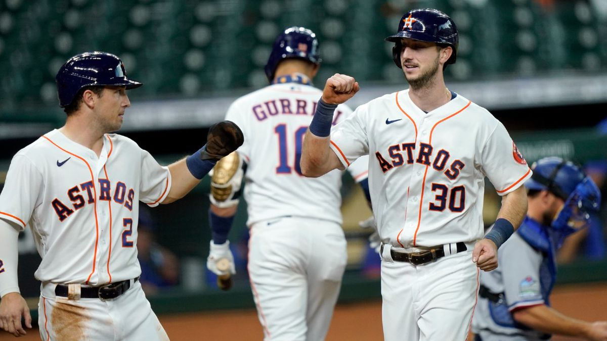 Houston Astros' Kyle Tucker (30) celebrates with Alex Bregman (2) after both scored on Tucker's...
