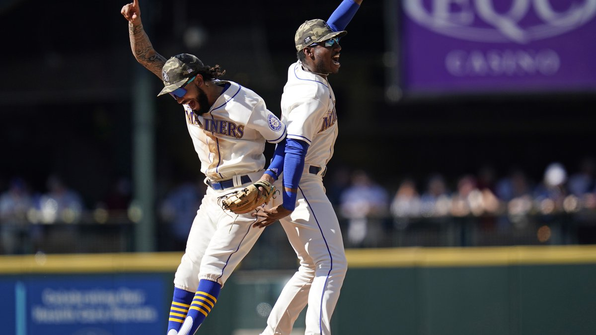 Seattle Mariners J.P. Crawford, left, and Kyle Lewis leap back-to-back as they celebrate the...