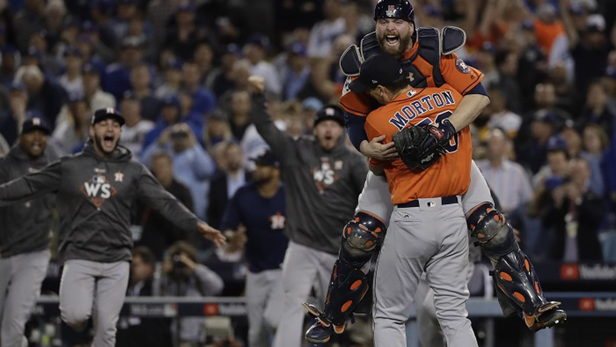 Houston Astros catcher Brian McCann leaps in the arms of starting pitcher Charlie Morton after...
