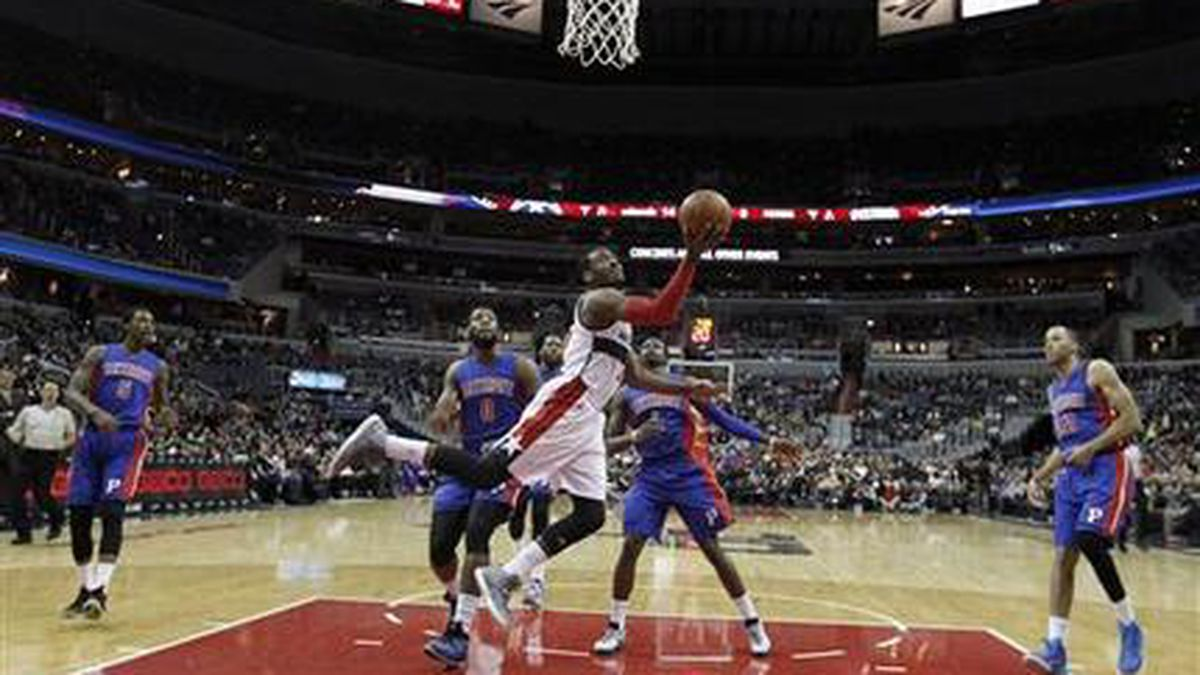 Washington Wizards guard John Wall (2) shoots in front of Detroit Pistons center Andre Drummond (0) and guard Reggie Jackson (1) in the first half of an NBA basketball game Saturday, Feb. 28, 2015, in Washington. The Wizards won 99-95. (AP Photo/Alex Brandon)