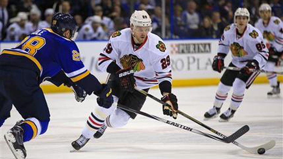 Chicago Blackhawks' Bryan Bickell, front right, brings the puck down the ice as St. Louis Blues' Ian Cole defends during the first period of an NHL hockey game Sunday, Feb. 8, 2015, in St. Louis. (AP Photo/Billy Hurst)