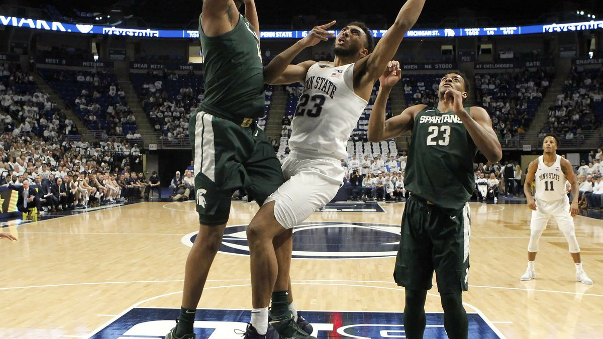 Penn State's Josh Reaves (23) goes to the basket as Michigan State's Nick Ward (44) defends...