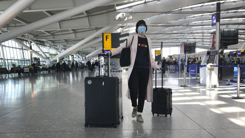A woman wears a mask as she walks at Heathrow Airport Terminal 5, in London, Tuesday, March 24,...