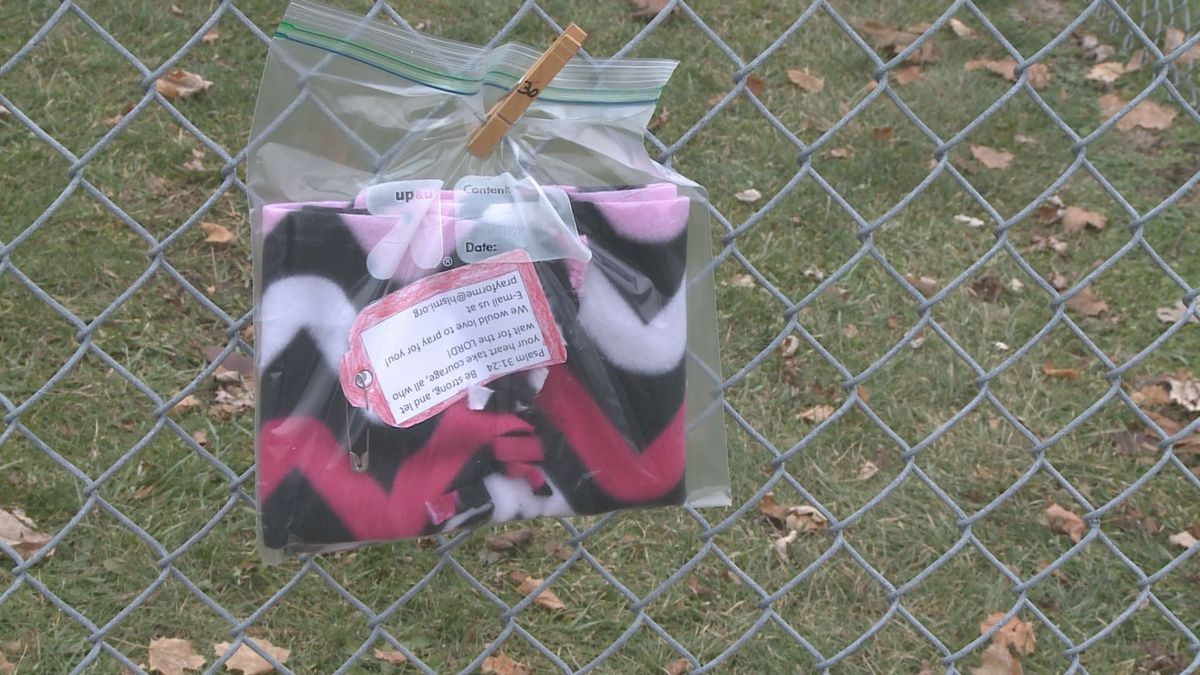 A pink and black chevron scarf is clothespinned onto a fence just outside Holt Lutheran's playground (source, WILX).