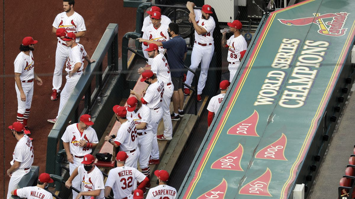 In this July 24, 2020, file photo, members of the St. Louis Cardinals wait to be introduced before the start of a baseball game against the Pittsburgh Pirates in St. Louis. The Cardinals 4-game series against the Detroit Tigers was postponed Monday, Aug. 3, 2020, after more Cardinals players and staff staffers test positive for COVD-19. The series was to have been played in Detroit from Tuesday through Thursday.