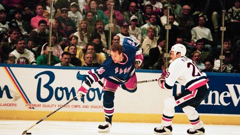 New York Islanders defender Tom Kurvers, right, tries to trip up New York Rangers center Craig...