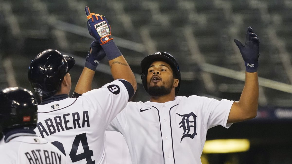 Detroit Tigers' Jeimer Candelario, right, celebrates with Miguel Cabrera after they scored on...