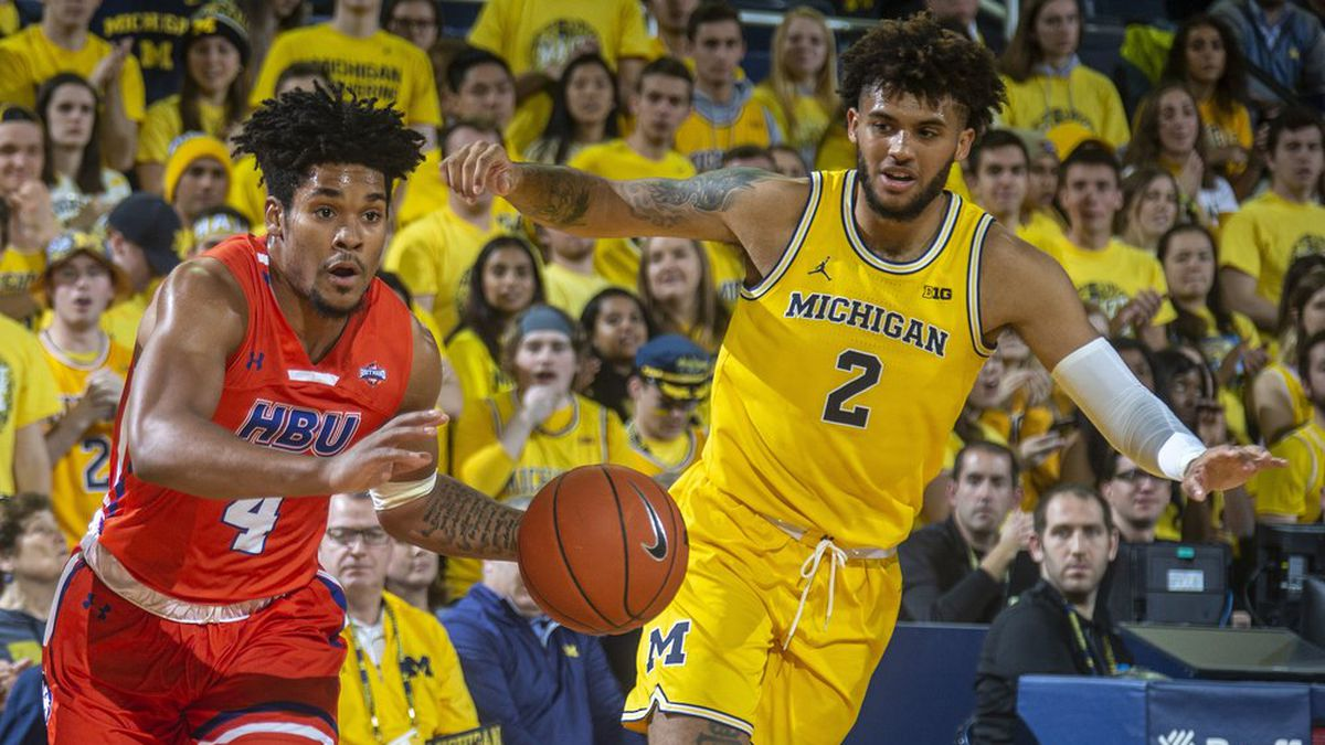 Houston Baptist guard Myles Pierre (4) dribbles the ball while defended by Michigan forward Isaiah Livers (2) during the first half of an NCAA college basketball game in Ann Arbor, Mich., Friday, Nov. 22, 2019. (AP Photo/Tony Ding)