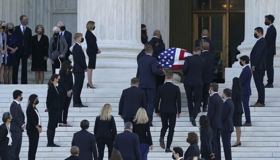 The flag-draped casket of Justice Ruth Bader Ginsburg arrives at the Supreme Court in Washington, Wednesday, Sept. 23, 2020. Ginsburg, 87, died of cancer on Sept. 18. Former law clerks of Ginsburg line the stairs.