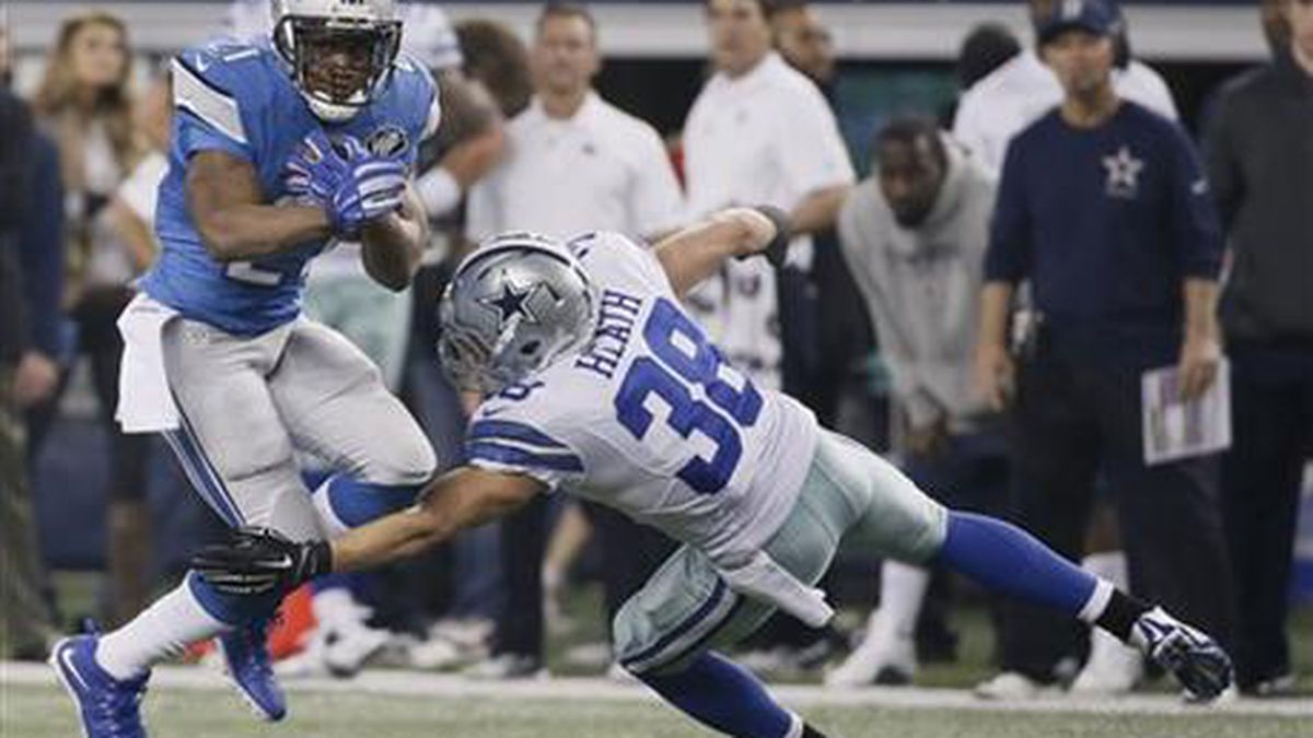 Detroit Lions running back Reggie Bush (21) is tackled by Dallas Cowboys strong safety Jeff Heath (38) during the second half of an NFL wildcard playoff football game, Sunday, Jan. 4, 2015, in Arlington, Texas. (AP Photo/Tony Gutierrez)