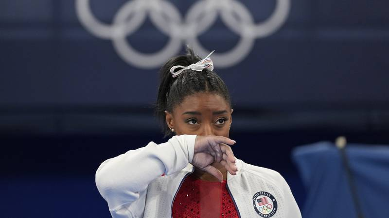 Simone Biles, of the United States, watches gymnasts perform after an apparent injury, at the...